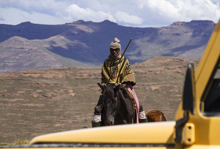 A shepherd on horseback approaches a yellow 4x4 near Thabana Ntlenyana.